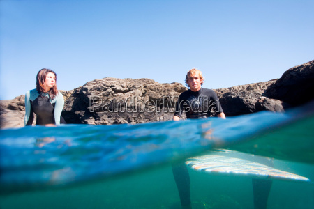 couple sitting on surfboards