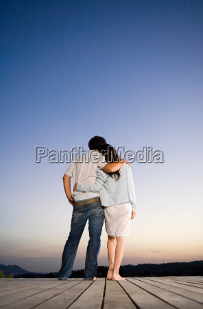 couple being affectionate on a dock