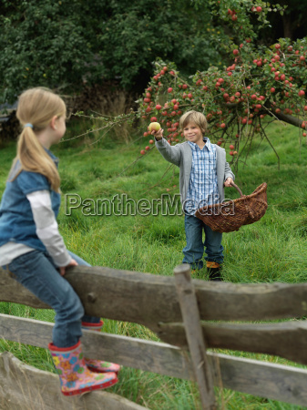 boy showing apple to girl on
