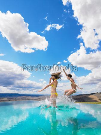 women jumping in swimming pool