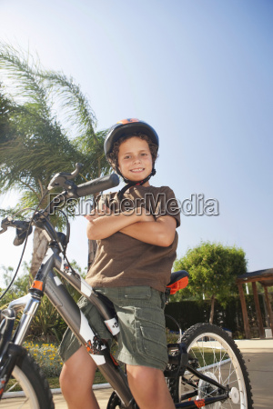 young boy sitting on bicycle smiling