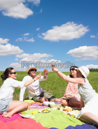 young people on blanket in field