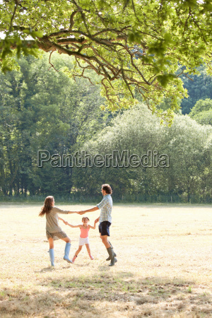 family playing together in country field