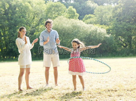 family playing with hoop in field