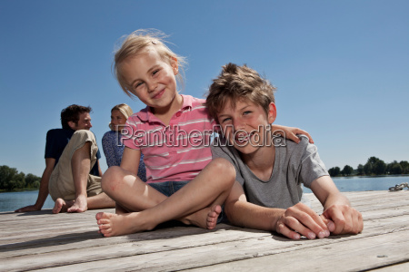brother and sister relaxing on dock
