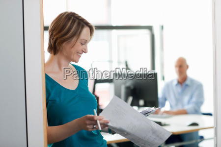 businesswoman reading papers in office
