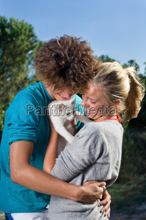 young couple group hug with kitten