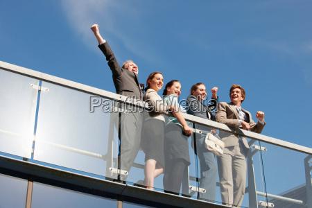business people cheering on walkway