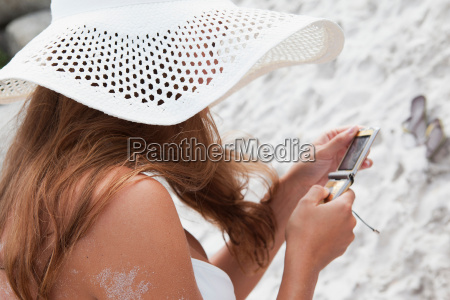 woman on beach using cell phone