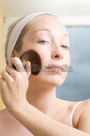 woman brushing powder onto her face