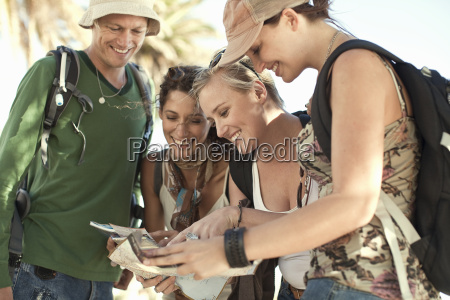 four young adult friends looking at