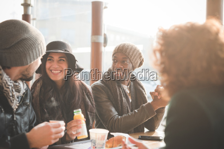 four young adult friends chatting at