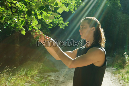 young man holding leaf in forest