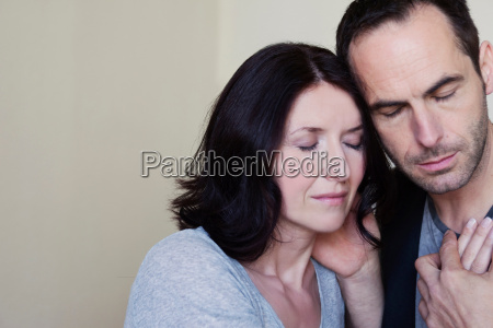couple holding hands eyes closed