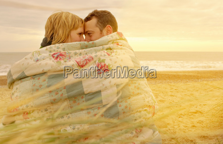 couple cuddling under blanket on beach
