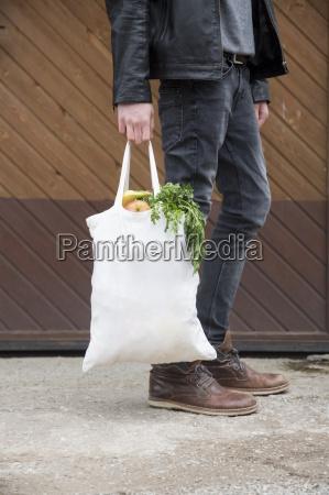adolescente llevando bolsas de compras reutilizables