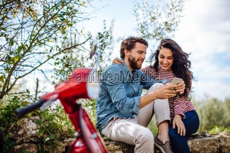 pareja joven sentado en pared en
