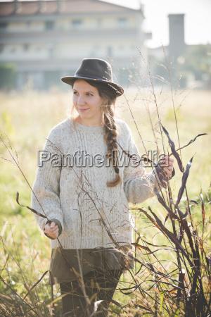 mujer joven con sombrero tocando plantas