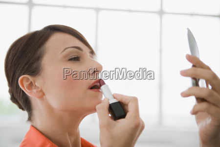 woman applying lipstick in a mirror