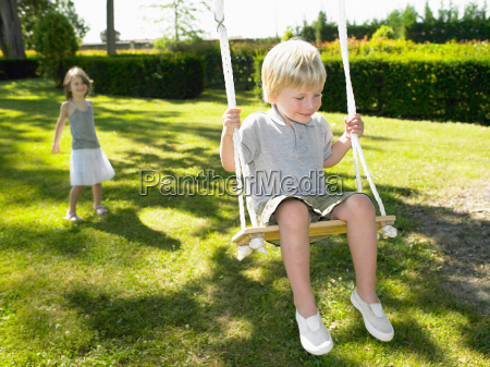 boy on a swing pushed by