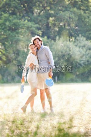 couple with rackets in country field