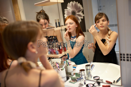 teenage girls applying make up