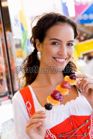 young woman eating candied fruits