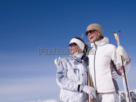 two women with skis smiling