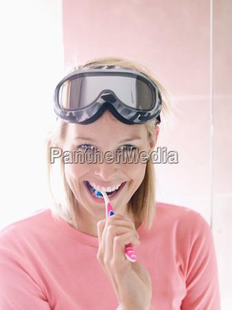 woman in ski gear brushing teeth