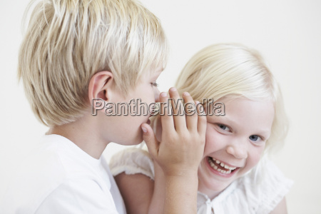 young boy whispering into girls ear