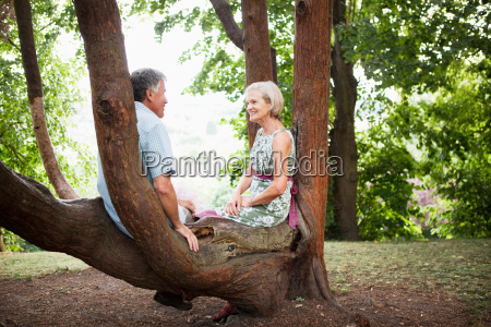 mature couple sitting in tree relaxing