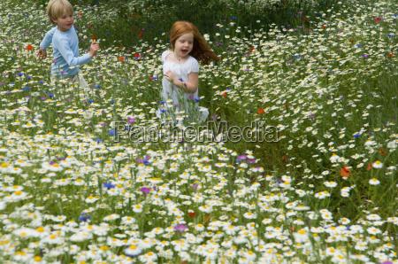 children running in field of flowers