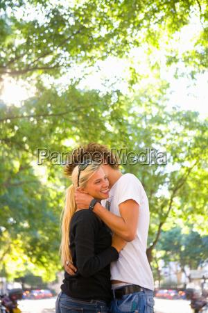 young loving couple share hug outside