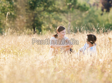smiling couple relaxing in wheatfield