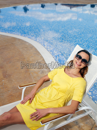 woman wearing sunglasses on sun bed