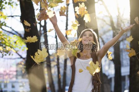 mujer adulta media lanzando hojas de