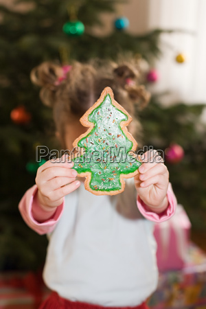 a girl holding a cookie