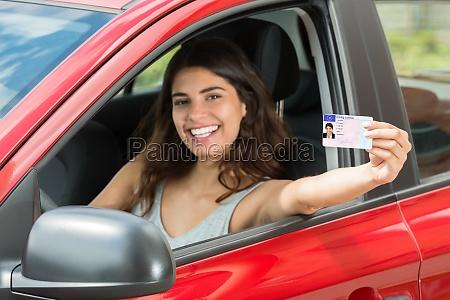 mujer mostrando su licencia de conducir