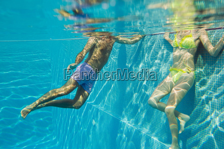 young couple in swimming pool underwater