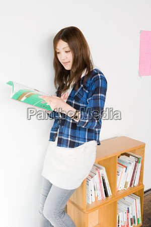 young woman looking at design book