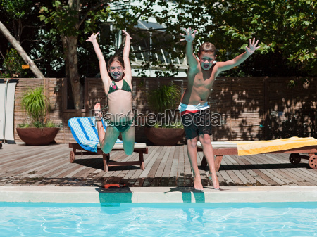 boy and girl jumping into swimming