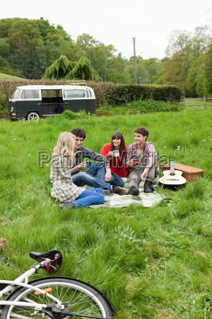 friends sitting in field by camper
