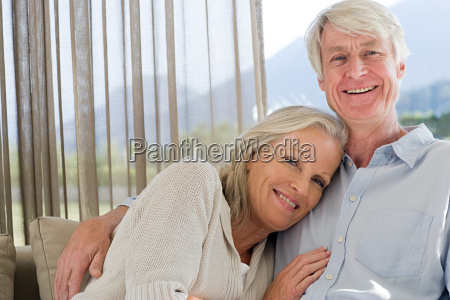 middle aged couple relaxing on couch