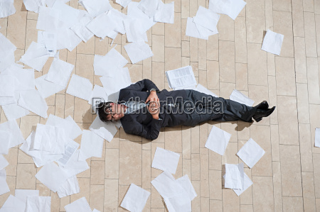 businessman lying on floor with scattered