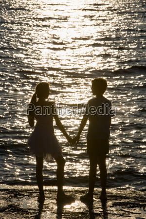 teenage couple watching sunset over sea