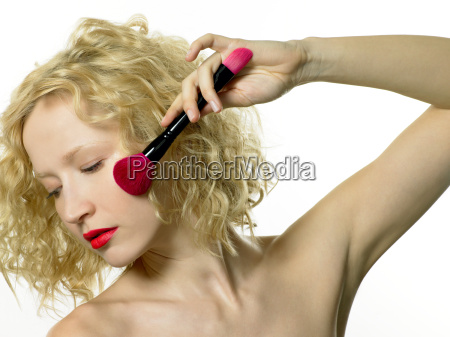 young woman applying blusher with make