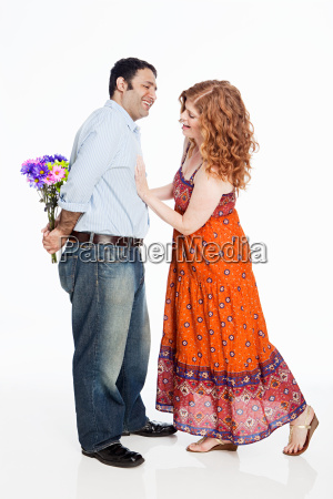 woman looking for flowers behind mans