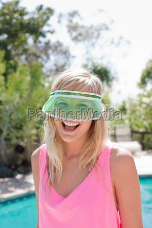 young woman wearing green sun visor