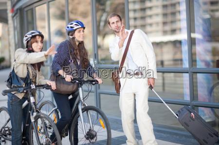 mujeres jovenes con bicicletas pidiendo direcciones