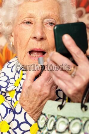 elderly woman applying lipstick